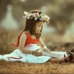 a girl sitting in the grass reading